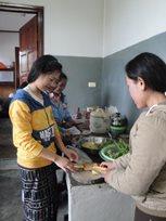 Kinder und ihre SOS-Mutter bereiten das Mittagessen vor (Foto: SOS-Archivi).
