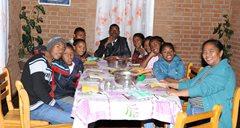 Eine SOS-Familie setzt sich zu einer gemeinsamen Mahlzeit hin (Foto: SOS-Archiv).
