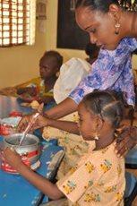 Eine Lehrerin hilft einem kleinen Mädchen im SOS-Kindergarten in Dosso (Foto: SOS-Archiv).