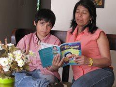 Ein Junger liest mit seiner SOS-Mutter (Foto: SOS-Archiv)